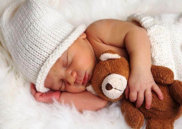 foto neonato abbracciato al peluche
